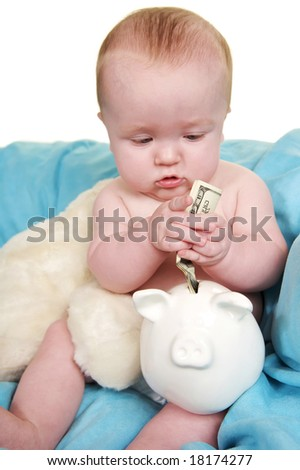 Up Close of cute baby putting money in a piggy bank - stock photo
