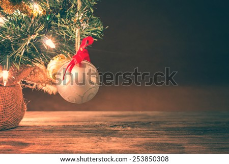 up-close silver christmas ball hanging from branch with a red bow with a instagram filter (shallow depth of field) - stock photo
