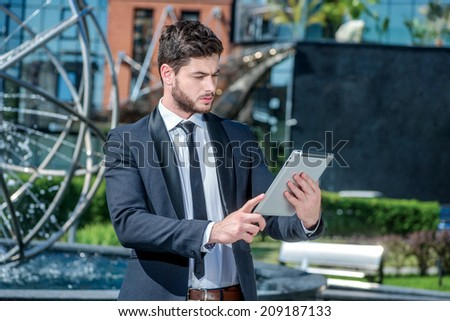 Up on the tablet. Confident and successful businessman holding a tablet and stands near the business center and looks aside.