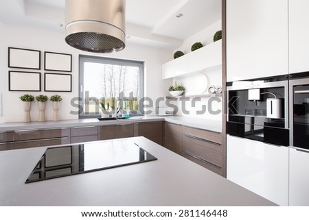 Up-to-date decor of kitchen with hob on island - stock photo