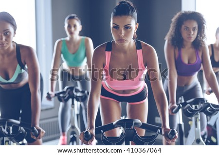 Up to speed with their fitness goals. Young beautiful women with perfect bodies in sportswear looking at camera while cycling at gym - stock photo