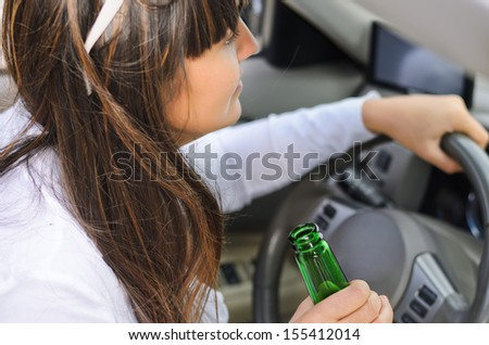 Up view of the hand of a woman drinking while driving gripping a green bottle bear - stock photo