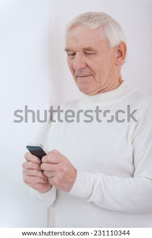 Up with times. Confident senior man holding mobile phone while leaning at the wall - stock photo