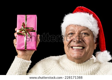 Upbeat smiling male senior lifting up an oblong present wrapped in pink and decorated with golden bowknot. Casual pullover and red pointed cap with pompon. Party mood and gift giving occasion. - stock photo