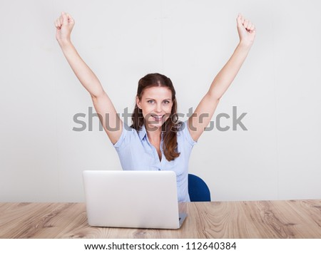 Upbeat successful young woman sitting at her laptop making a fist of jubilation and celebration