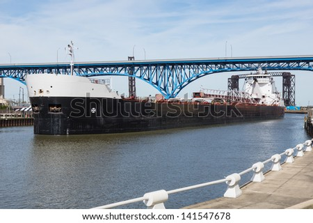 Upbound On The Cuyahoga:  A Great Lakes bulk carrier moves slowly upbound on the Cuyahoga River at Cleveland, Ohio - stock photo