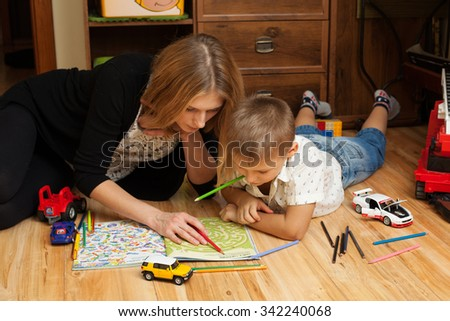 upbringing and education - mother and son are playing on the floor in the room - stock photo