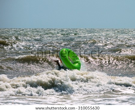 upheaval of children's inflatable circle on the wave of the sea, the foot of the water - stock photo