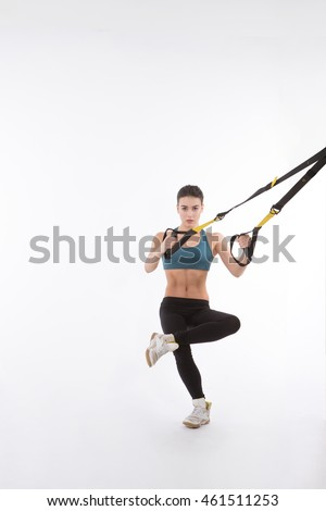 Upper body exercise concept. Picture of beautiful fitness trainer or coach showing her strong body with muscles. Pretty lady training with suspension trainer sling isolated on white background.