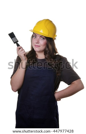upper body studio shot of a pretty model wearing a yellow hard hat on her head and holding a paint brush in her right hand.