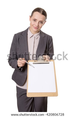 Upper body studio shot of a young happy business woman, holding a clipboard and pen towards the camera.  - stock photo