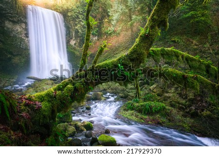 Upper Bridal Veil falls along the beautiful Columbia River Gorge at sunrise.  The rays and greens give the location a magic feeling.  - stock photo