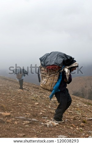 UPPER DOLPO, NEPAL - SEPTEMBER 12: Porters carry heavy load in the Himalaya in time of the Russian ethnographic Expedition on September 12, 2011 in Upper Dolpo restricted area, Nepal