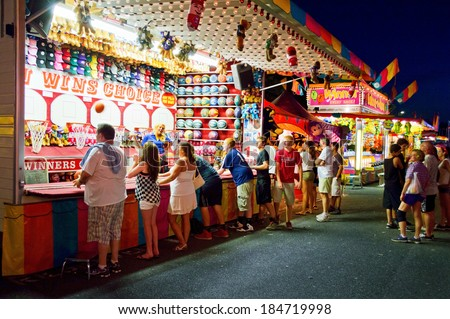 UPPER FREEHOLD, NEW JERSEY/USA -Â?Â? July 14: Teenagers at a carnival game at the Freedom Fest in Upper Freehold on July 14 2013 in New Jersey. The state fair is an annual event in Central New Jersey. - stock photo