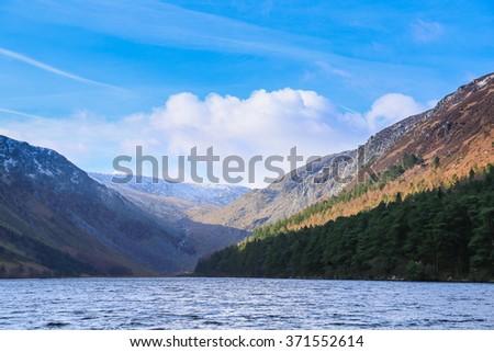 Upper lake valley on a sunny day in wintertime in Glendalough in Ireland - stock photo