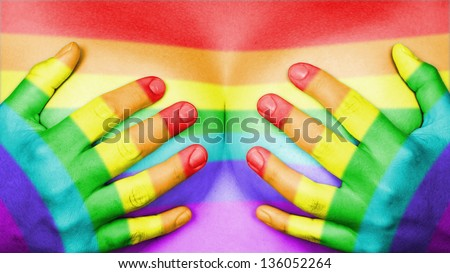 Upper part of female body, hands covering breasts, rainbow flag - stock photo