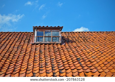 Upper part of medieval tile roof with window with a blue sky back - stock photo