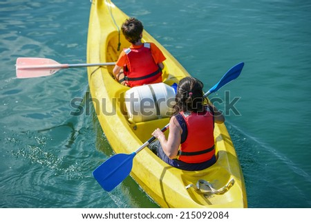 Upper shot of two young people canoeing in the lake - stock photo
