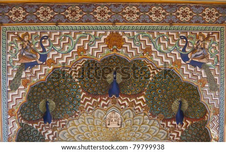 Upper structure of Peacock gate at Jaipur's Royal palace. Multiple peacocks with full tail decorate elaborate artwork on top of door. - stock photo