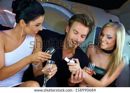 Upper ten having fun in luxury car, drinking champagne, smoking cigar. - stock photo