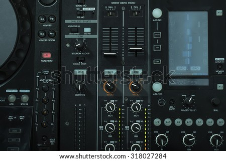 Upper view closeup of dj musical mixer electronic professional console black color with many buttons and knobs in night club or studio on digital background, horizontal picture - stock photo