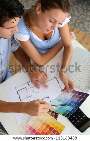 Upper view of couple looking at colour chart - stock photo