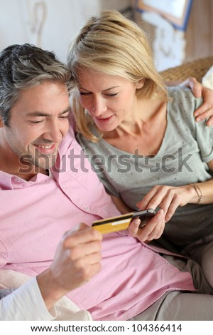 Upper view of couple paying with credit card on mobile phone - stock photo