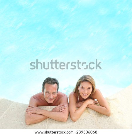 Upper view of couple relaxing in resort pool - stock photo