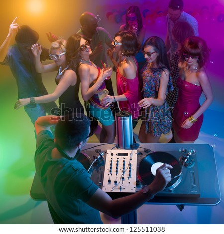 upper view of dj standing and playing music with turntables at a party with colorful lights and happy young people dancing with sunglasses and soap bubbles