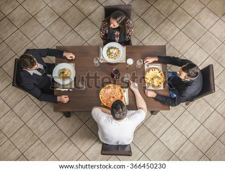 Upper view of four friends at a table in a restaurant.