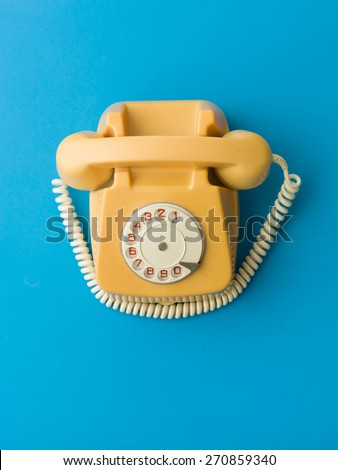 upper view of yellow vintage phone on blue background - stock photo