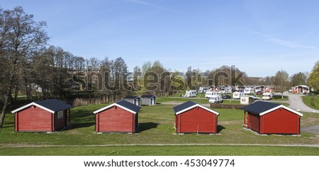 UPPSALA, SWEDEN ON MAY 06. View of lodges, caravans and campers in Fyrishov camping on May 06, 2016 in Uppsala, Sweden. Red small buildings for rent. Morning.