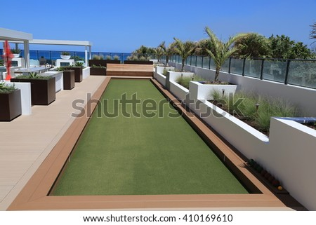 Upscale artificial turf bocce ball court on an outdoor oceanfront terrace.