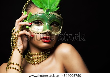 Upscale Indian woman wearing gold jewellery and red lipstick on black background. Green party mask.