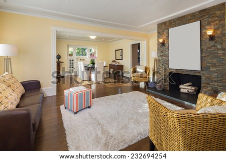 Upscale living room with rug, brown leather couch, bamboo chairs, recessed lighting, and fireplace adjacent to library and dining room. - stock photo