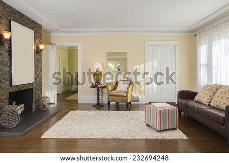 Upscale living room with rug, brown leather couch, recessed lighting, and fireplace adjacent to library and dining room. - stock photo