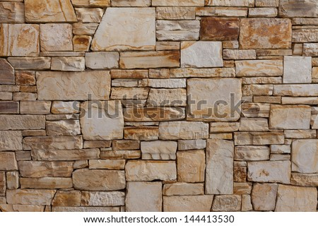 Upscale natural stone wall pattern or background, constructed with a high level of craftsmanship. Marble, granite, slate stone material. Gray and some beige, brown stone pieces, slabs or bricks. - stock photo