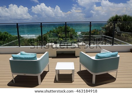 Upscale outdoor terrace with designer furniture overlooking the ocean.