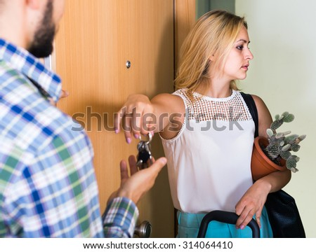 Upset american adult watching how spouse moving out with baggage - stock photo