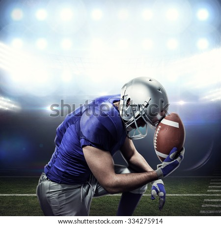 Upset American football player with ball against american football arena
