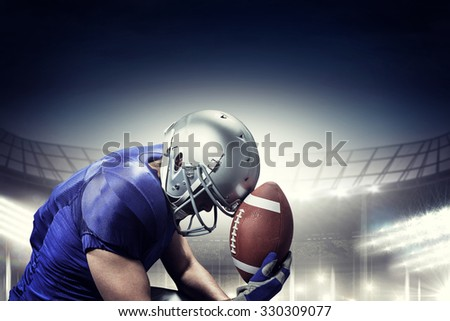 Upset American football player with ball against rugby stadium