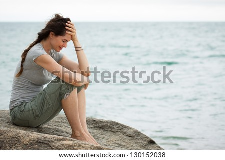 Upset and depressed woman sitting by the ocean crying with her head in her hand. - stock photo