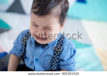 Upset and sad cute 11 month old mixed race Asian Caucasian boy dressed in braces and bow tie plays cheerfully on a colourful geometrically shaped bed cover - stock photo