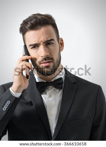 Upset angry unshaven man talking on the phone looking away. Portrait over gray studio background.  - stock photo