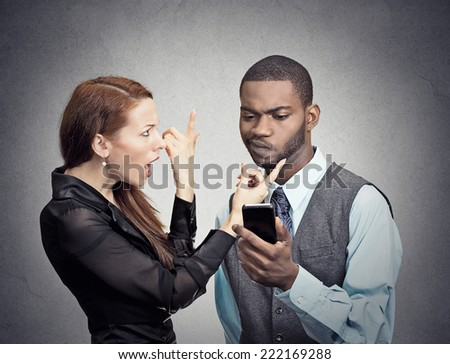 Upset angry woman trying to bring attention of young handsome man ignoring her looking at smartphone reading browsing internet isolated grey wall background. Phone addiction concept. face expression - stock photo