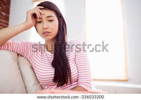 Upset asian woman on couch at home in the living room - stock photo