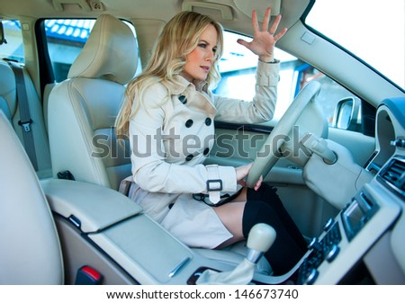 upset attractive woman in driver seat of her car - stock photo