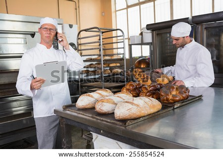 Upset baker making phone calls in the kitchen of the bakery