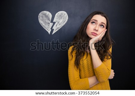 Upset beautiful young woman standing and thinking over background of chalkboard with drawn broken heart - stock photo