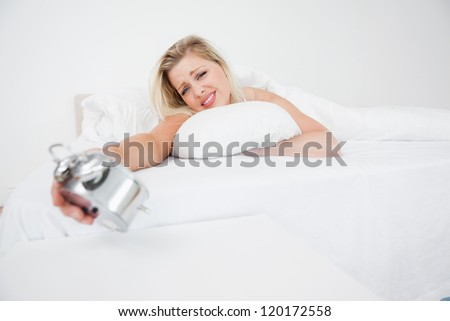 Upset blonde looking at her alarm clock while lying in her bed - stock photo